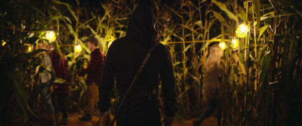 An armed figure in black walks into a corn maze