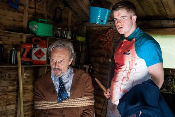 A teen in a blood covered shirt holds a wooden stake next to an old man tied to a chair