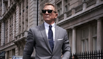 A suave blonde man in a grey suit and sunglasses