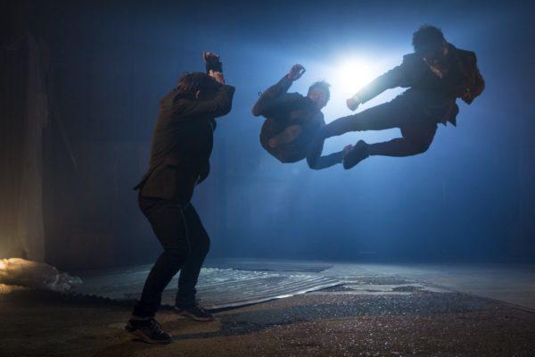 A man kicks another man in mid-air as a third man watches