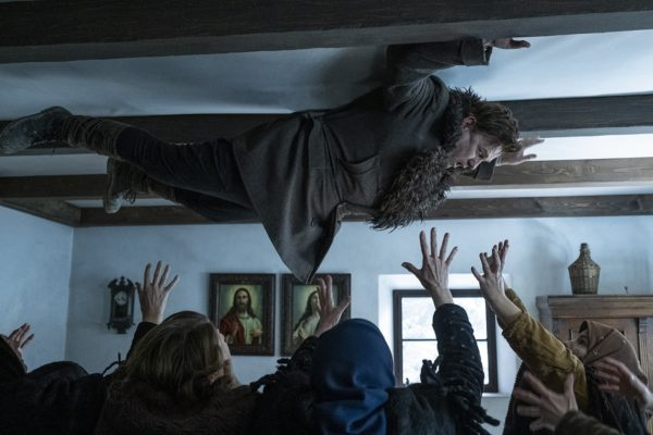 A man is pinned to the ceiling as people reach for him