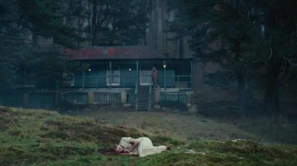 A woman in a white nightgown lays on the ground in front of a cottage in the woods